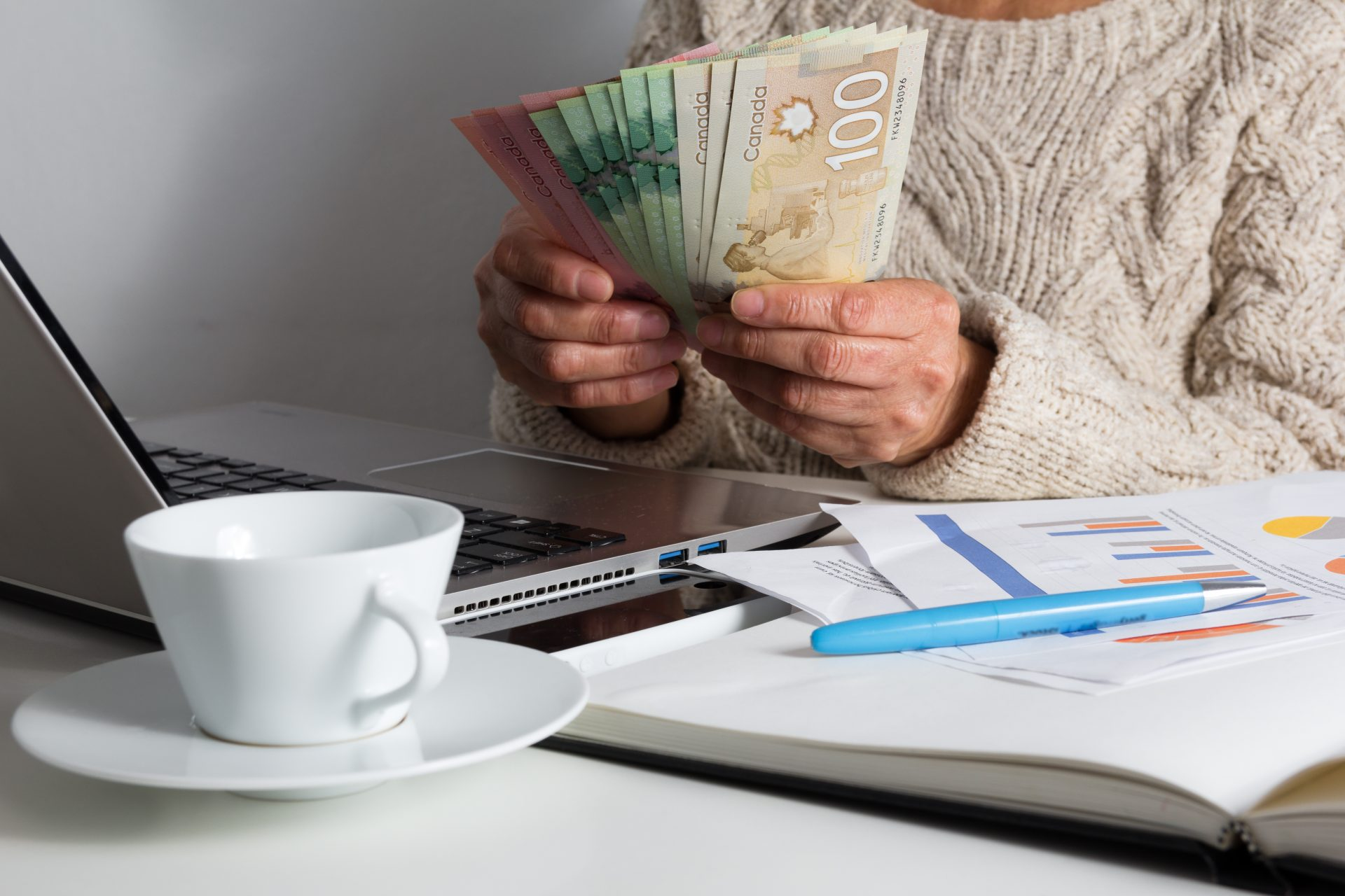 Woman counting Canadian money beside a laptop, coffee mug, and spreadsheets